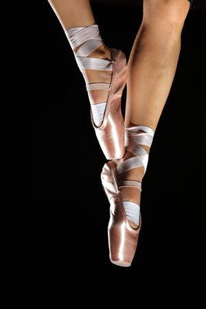 pointes: foots with pointes of ballet dancer isolated on black Stock Photo