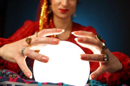 gitana: manos de un vidente trabaja con una bola de cristal brillante