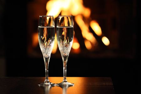 two glasses in front of fireplace photo