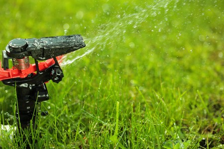 rotational: closeup of lawn sprinkler with copyspace Stock Photo