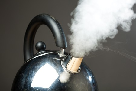 boiling kettle with dense steam photo