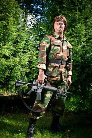cazador: soldado sosteniendo la pistola  Foto de archivo