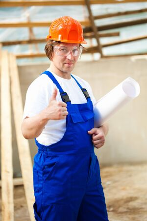 smiling builder holding thumbs up photo