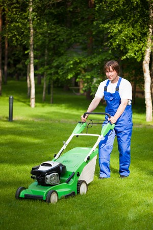mowing lawn: lawn mover man working on the backyard Stock Photo