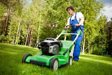 gras maaien: gazon verhuizer man aan het werk op de achtertuin Stockfoto