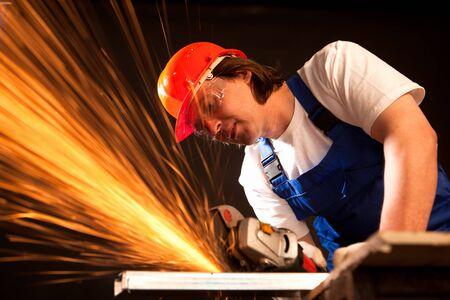 industrial worker: worker cutting metal