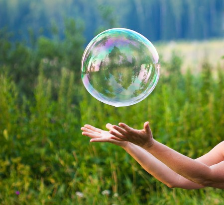 bubble background: hand catching a soap bubble Stock Photo