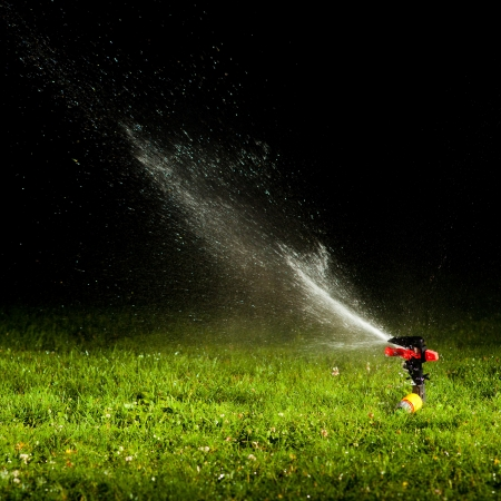 irrigation equipment: lawn sprinkler spraying water over green grass at night