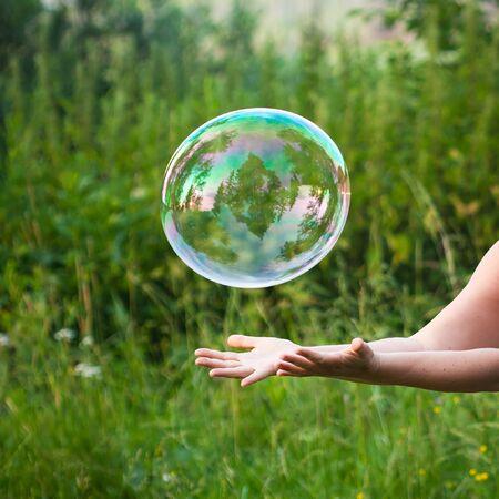 soap bubbles: hand catching a soap bubble Stock Photo