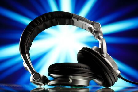 headphones against blue rays background Stock Photo - 8119659