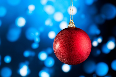 red Christmas decoration against blue defocused background photo
