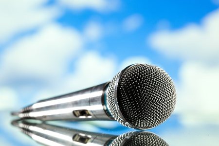 microphone against blue cloudy sky background photo