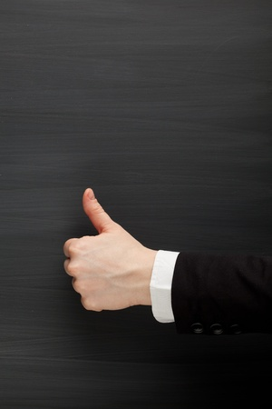 thumbs up against blackboard background Stock Photo - 8838527