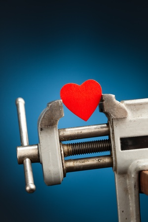 holiday stress: heart healing concept - red heart in the vice tool