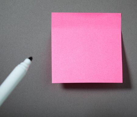 pink sticky paper on the grey wall photo
