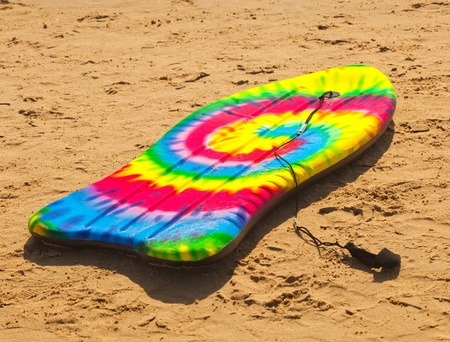 surf board laying on the sand photo