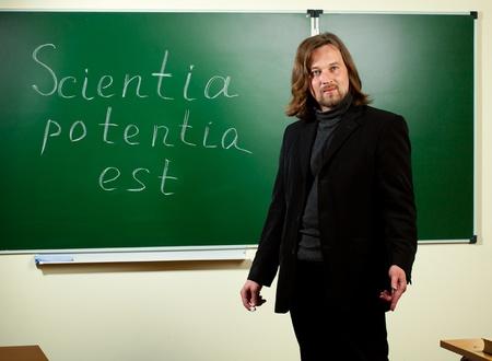 est: young teacher against blackboard background Stock Photo