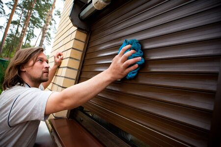 security shutters: man cleaning roller shutters