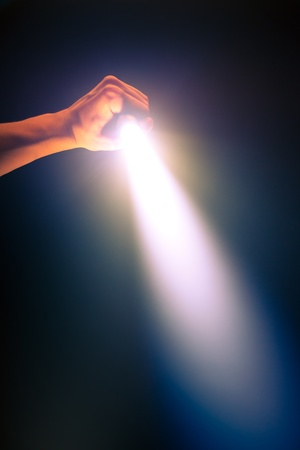 searchlight: hand holding glowing pocket torch light Stock Photo
