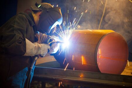 skilled labour: welder at factory work