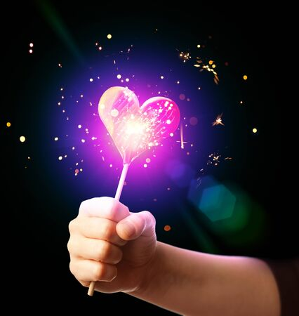 lollypop: hand holding sparkling candy heart