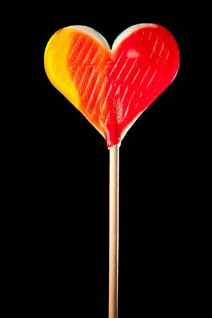 lollypop: candy heart isolated on black
