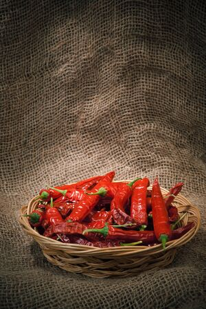 red chili peppers on the wicker dish, sacking background photo