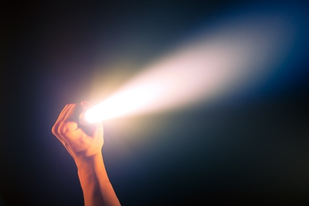 hand holding glowing pocket torch light Stock Photo