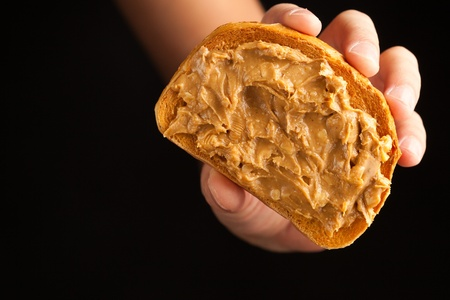 peanut butter toast bread in hand on black background photo