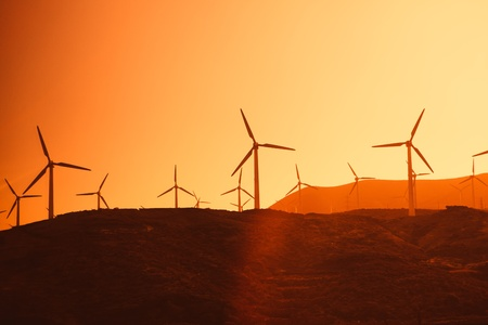 Electric wind turbines farm silhouettes on sun background photo