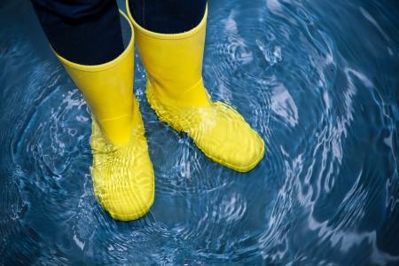 zapatos de seguridad: botas de goma en el agua Foto de archivo