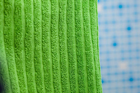 green towel against blue tile background photo