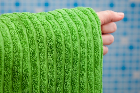 hand holding green towel against blue tile background photo