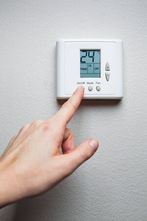 hand turning on digital climate control