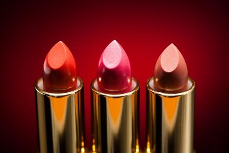 lipstick tube: three lipsticks on red background