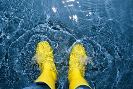 botas de lluvia: botas de goma chapoteando en el agua