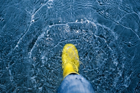 puddle: rubber boot splashing in the water Stock Photo