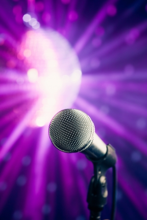 volume glow light: microphone against violet disco background Stock Photo