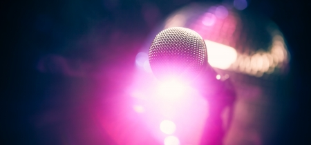 volume glow light: microphone on stage against purple background