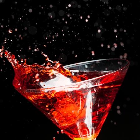 martini splash: red splashing cocktail on black