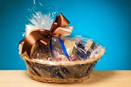 süssigkeiten: Geschenk in einem Korb vor blauem Hintergrund