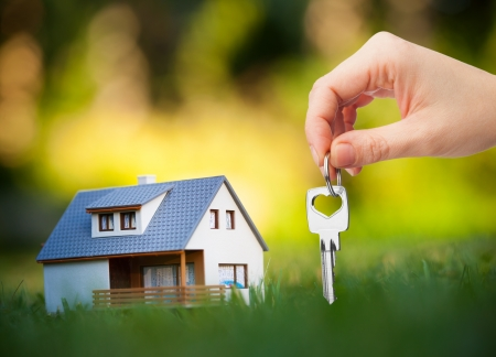 hand holding key against house background photo