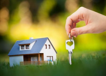 house key: hand holding key against house background