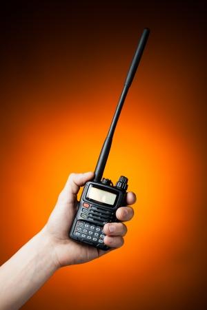 cb: professional walkie-talkie radio in hand on orange background