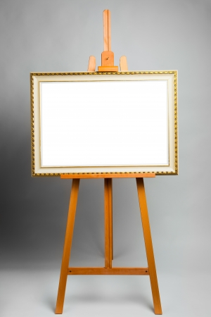 easel with painting frame on grey background photo