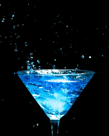 blue splashing cocktail on black photo