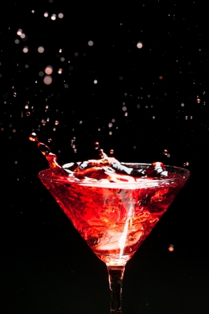abstract liquor: red splashing cocktail on black