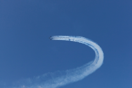 white trails of a jet fighters on blue sky photo