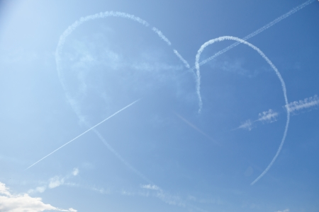 supersonic transport: heart shaped trail of a jetfighter on blue sky