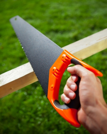 handsaw: cutting plank with hand saw Stock Photo